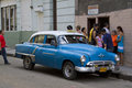 Old blue classic car working as a taxi picking up passengers in havana cuba past international embargoes have meant cuba has Royalty Free Stock Photography