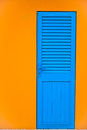 The old blue door in orange wall Royalty Free Stock Photography