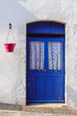 Old blue door in a white stucco worked wall and a red flowerpot Stock Photos