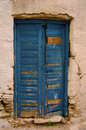 Old blue door an in wood planks with cracked white ciment wall around it seen in paros island greece Royalty Free Stock Image