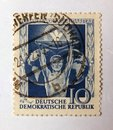 An old blue east german postage stamp with an image of a man depicting solidarity behind a globe of the world Royalty Free Stock Photo