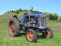 Old blue farm tractor in field. Royalty Free Stock Photo