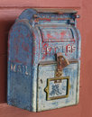 Old blue mailbox on a door close up of an weathered and worn metal with peeling paint red wooden Royalty Free Stock Image