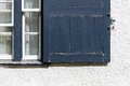 Old Blue Peeling Paint Vintage Window Shutter on White Wall Royalty Free Stock Photo