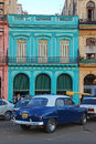 Old blue plymouth car in front of colourful building in cuba vintage havana the evening Royalty Free Stock Photography