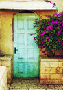 Old blue rustic wooden door and flowers. filtered image with texture overlay Royalty Free Stock Photo