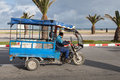 Old blue tricycle cargo bike tangier morocco march with arab driver rides on the coastal street of tangier this is traditional Royalty Free Stock Image