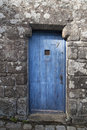 Old blue wooden door in a stone wall Royalty Free Stock Photo