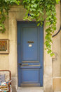 Old blue wooden entrance door to the house with creeper mediterranean architecture Stock Photography