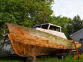 Old boat repair a run down vintage wooden propped up on blocks on dry land being repaired Stock Images