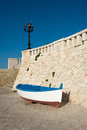 Old boat resting on harbor wall with blue sky and street lamp Stock Images