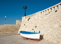Old boat resting on harbor wall with blue sky and street lamp Royalty Free Stock Photography