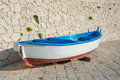 Old boat resting on harbor wall in with stone in background Royalty Free Stock Photos