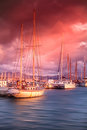 Old boat on the sea in the port at sunset bright colorful dramatic sky Stock Photos