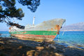 Old boat stranded on the shore cargo rocks in croatia Royalty Free Stock Photos