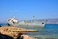 Old boat stranded on the shore cargo rocks in croatia Royalty Free Stock Photo