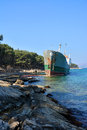 Old boat stranded on the shore cargo rocks in croatia Royalty Free Stock Photo