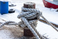 Old bollard and frozen ship cable under snow at the pier in winter Royalty Free Stock Photos