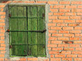Old bolted wooden window shutters on red brick wall Royalty Free Stock Photo