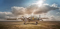 Old bomber in cloud of dust in the open field Stock Photo