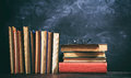 Old books and eye glasses on blackboard background Royalty Free Stock Photo