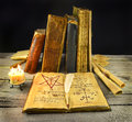 Old books with necronomicon halloween still life of book library burning candles and paper scrolls Royalty Free Stock Photo