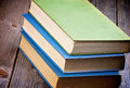 Old books pile of three isolated on rustic wooden background Stock Photos
