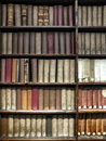 old books stacked on wooden shelves Royalty Free Stock Photo
