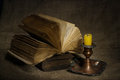 Old books with yellow candle on canvas background Royalty Free Stock Photo