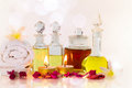 Old bottles of aromatic oils with candles, flowers, towel on glossy white table Royalty Free Stock Photo