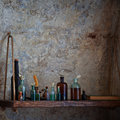 Old bottles of various liquids on the shelf pharmacist s bottle with against dilapidated walls Stock Photography