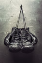 Old boxing gloves hang on nail Royalty Free Stock Photo