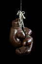 Old boxing gloves hanging on black background isolated Royalty Free Stock Images