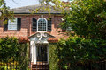 Old brick home beyond black wrought iron gate a classic vine covered a fence and Stock Photos
