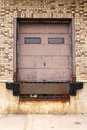 Old Brick and Rusty Metal Truck Loading Dock Door to Warehouse Royalty Free Stock Photo