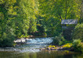 Old brick wall shed, green summer trees.  Rapids of babbling water flow in a scenic woodland setting. Royalty Free Stock Photo
