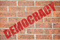 Old brick wall texture with democracy inscription red on brickwall surface pattern as a wallpaper concept for designers background Royalty Free Stock Image