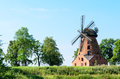 Old brick windmill on field on blue sky background stock photo Royalty Free Stock Photography