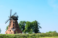 Old brick windmill on field on blue sky background stock photo Royalty Free Stock Photos
