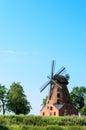 Old brick windmill on field on blue sky background stock photo Stock Photography