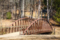 An old bridge across a stream in a public park in winter Royalty Free Stock Photo
