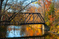 Old bridge an pedestrian over an autumn hued stream Stock Photo