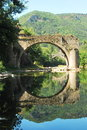 Old bridge reflecting in the river tarn ruins of over france close to little village of le rozier reflected mirroing waters of Royalty Free Stock Image