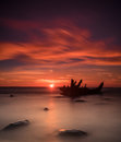 Image : Old broken boat wreck on the shore, a frozen sea and beautiful blue sunset background.