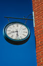 Old broken clock an alarm attach to a brick wall Royalty Free Stock Image