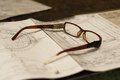 Old broken glasses on old and dirty blue prints for industrial manufacturing