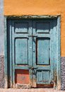 Old broken green bolted shut door in an abandoned house Royalty Free Stock Photo