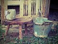 Old broken tin bucket and an aluminum pot over the stool Royalty Free Stock Photo