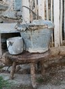 Broken tin bucket and an pot over the stool of the old stable Royalty Free Stock Photo