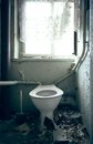 Old broken toilet an with window in background Royalty Free Stock Photos